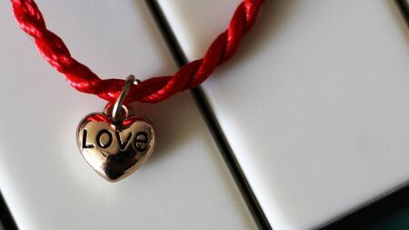 A heart of gold and a scarlet thread on piano, jewelry Imagens