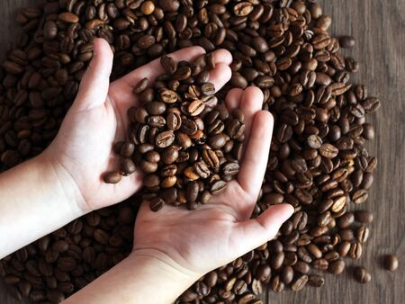 Roasted coffee beans in hands, homemade texture coffee background. Foto de archivo - 128256165