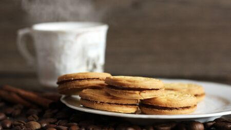 Round cookies with filling and a Cup of coffee Foto de archivo - 128256189