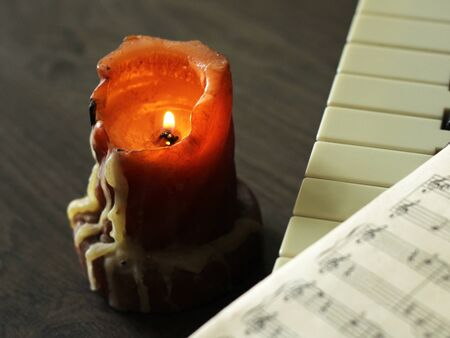 Old burning candle, sheet music and piano