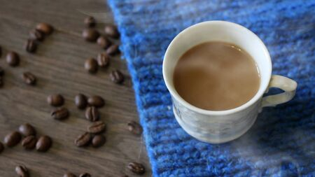 Cup of coffee surrounded the warm scarf Foto de archivo - 128256386