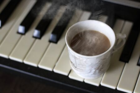 Cup of hot coffee on the piano Foto de archivo - 128256388