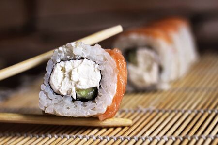 Delicious rice and fish rolls. Traditional Japanese cuisine. So close. Foto de archivo - 128256453