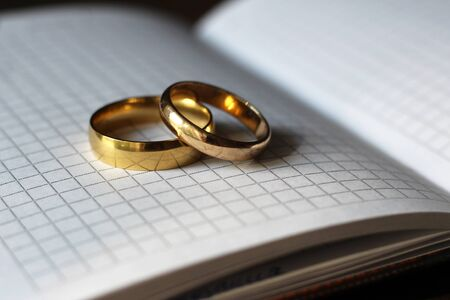 Two gold wedding rings and a paper notebook, love Imagens