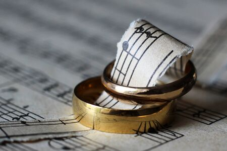 Two wedding rings and old musical notes so close Stock Photo