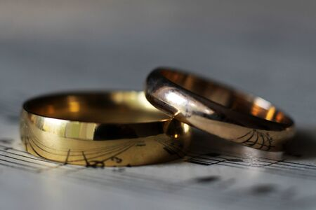 Two wedding rings and old musical notes so close Foto de archivo - 129626102