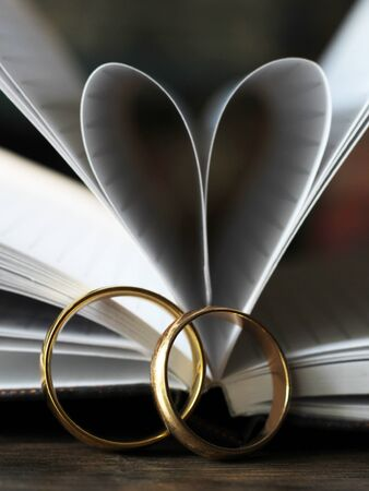 Two gold wedding rings and a heart made of paper pages so close Imagens