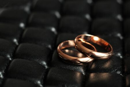 Gold wedding rings on leather fabric, love