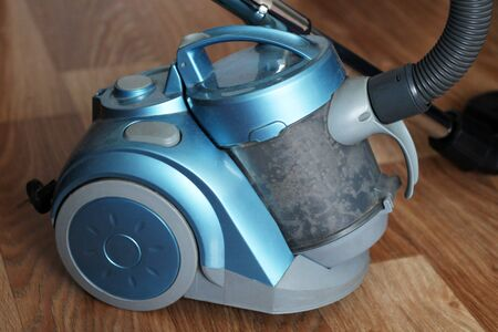 Blue vacuum cleaner on wooden floor so close Stock Photo