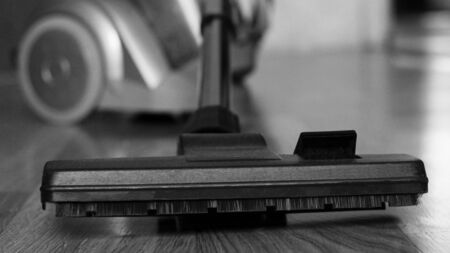 vacuum cleaner and dust on a wooden floor so close