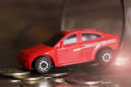 red car over a lot of golden coins so close