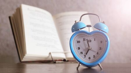 Blue Alarm clock and book on wooden table
