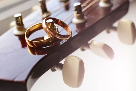 two gold wedding rings lie on guitar strings close-up, love and happy Stock Photo