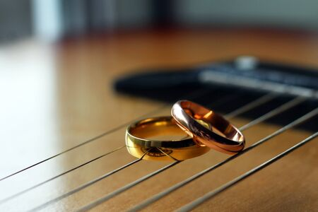 two gold wedding rings lie on guitar strings close-up, love and happy object Stock Photo