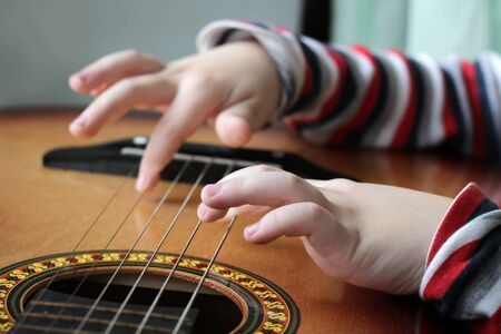 Guitar in the hands of a child of a little girl playing music. People.