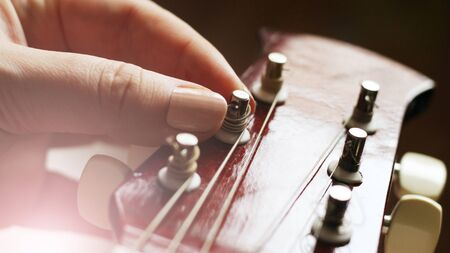 Female hand and guitar strings so close