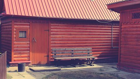 Old bench and wooden houses, vintage toned image