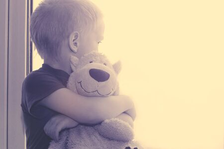 A little boy and a soft bear look out the window, toned