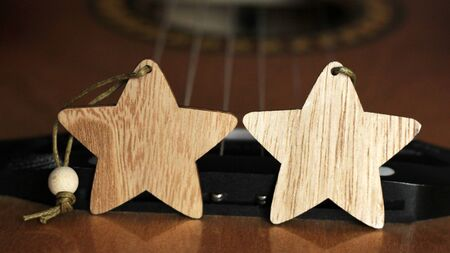Two wooden stars and a guitar so close
