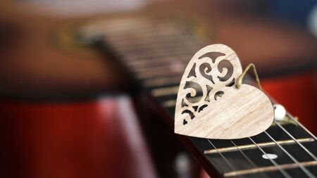 Wooden heart on the strings of the guitar so close Archivio Fotografico