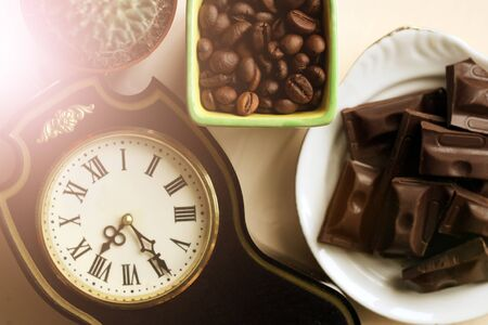 Retro clock with Roman numerals, coffee beans and chocolate, top view 스톡 콘텐츠