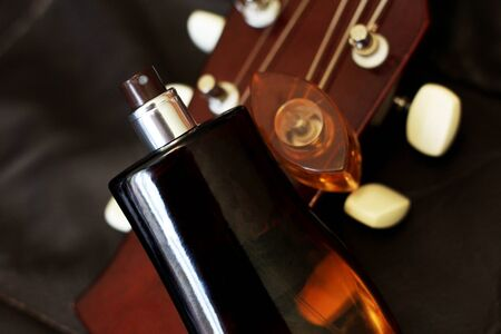 Men's glass perfume and guitar so close, brown color