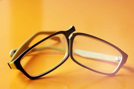 Broken yellow glasses on orange background so close
