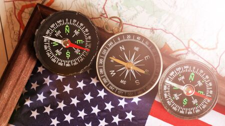 Three compasses and an American flag in a wooden frame, travel theme