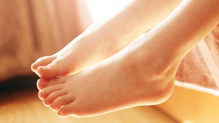 Children's feet in the sunlight, body parts so close