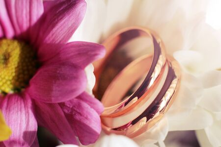 Golden wedding rings on bridal bouquet. Macro. Close-up