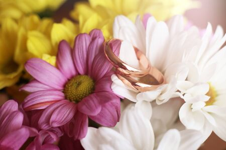 Closeup of wedding rings on flowers so close