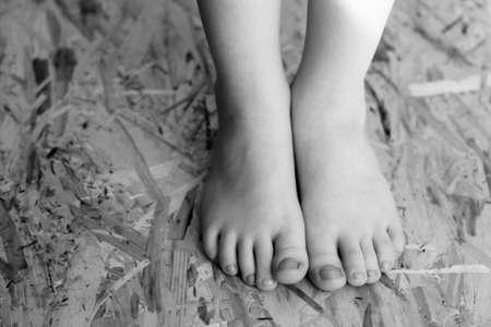 Children's feet on OSB material so close