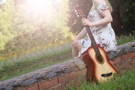 Beautiful girl and retro guitar in the garden, outdoor
