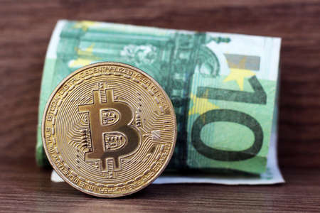 photo of golden bitcoin new virtual currency with traditional euro, wooden background, online work
