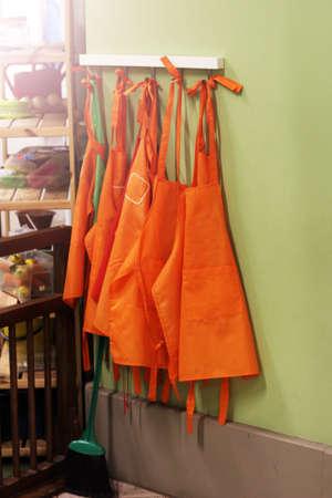 Orange aprons on a hanger, sunlight