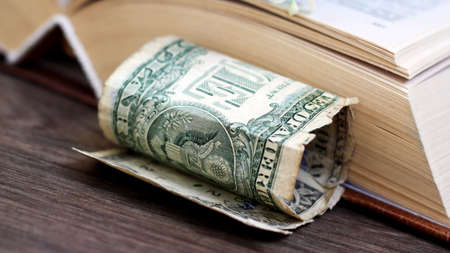 Old books with one dollar. Concept for buyng or selling books.