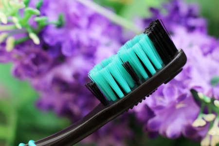 Green toothbrush with tiny flowers. Healthcare object.