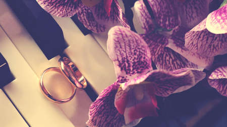Wedding rings on the piano and pink orchid so close