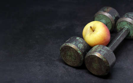 Old iron dumbbells and an apple, sports and diet. Dark background.