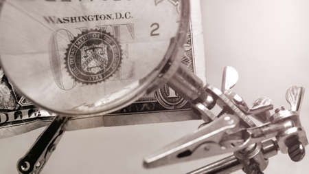 Money. Magnifier over money. US dollars under a magnifying glass. A dollar on a pair of tweezers in a pawnshop.