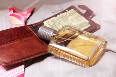 Men's perfume and wallet on a man's jacket, light toned