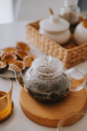 Teapot with tea on a wooden stand. Beautiful breakfast