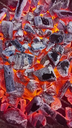 Hot red coals texture. Burning charcoals background. Close-up of a hot charcoals lying in a barbeque grill.