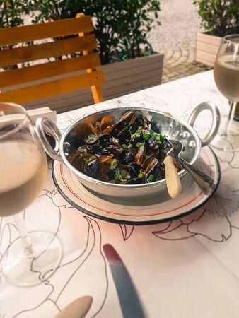 Bowl with boiled mussels. Moules in a white sauce. Appetizer and white wine.