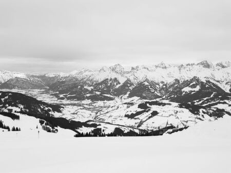 Snowy peaks of Alps, Austria. Peaceful black and white panorama of mountains in a cloudy day. Banque d'images - 140637137
