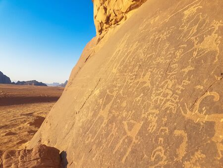 Sandstone rock with prehistoric art. Prehistoric civilization left their primitive drawings on limestone cliff in Wadi Rum desert, Jordan. Stone-age paintings.