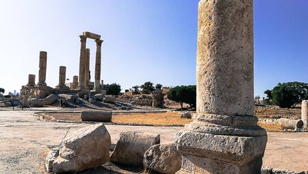 Ruined columns. Temple remains in the middle of Amman town. Stone pillar in front of the image. Roman civilization and its legacy.