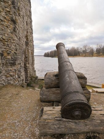 Old cannon that defended medieval fortification on the shore of river. Old ruined castle and its weapons. Historic gun made of steel.