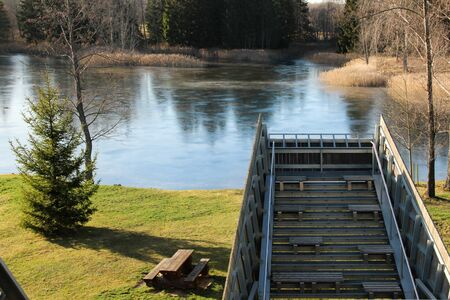 Part of an observation platform in front of the karst lake in Kirkilai national park, Lithuania. Resting and picnic spot outdoors at the lakeside in a sunny day. Imagens