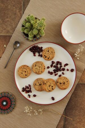 Top view of a plate with chocolate chip cookies and raisins. Tablecloth with arrangement on it. Reklamní fotografie